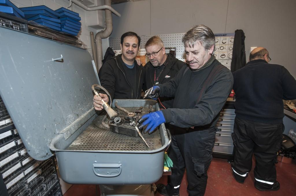 Kouluttaja Kai Ström opastaa kiinteistöalan oppilaita Heidaria ja Khlidia pienkoneiden huollossa. Kuva: Teija Hakala