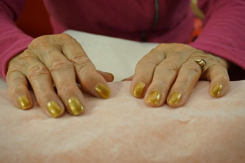 Nämä kädet ovat työllä kyllästetyt. Palvelutalon asukas toivoi punaisen sijaan kultaisia kynsiä.