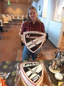 Omnian opiskelija Jenna Söderberg poseeraa Kokkikilta-vaakumam sekä leipomansa Kokkikilta-kakun kanssa.