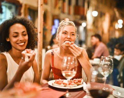 Naisia syömässä pizzaa