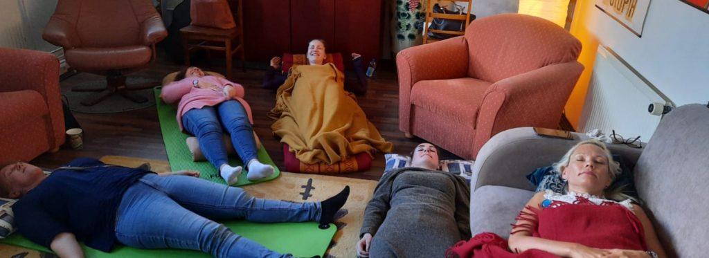 Ryhmärentoutus ihmiset rentoutuvat lattialla ja nojatuoleissa silmät kiinni
